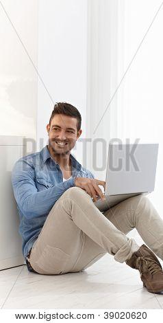Glücklich Jüngling sitzen auf Boden zu Hause, im Internet Surfen, mit Laptop-Computer.