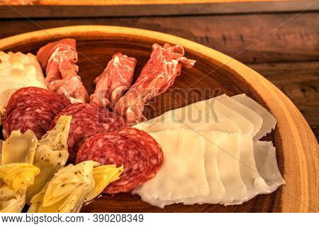 Charcuterie Board On Rustic Wood With Candles Behind A Spread Of Prosciutto