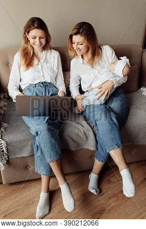 Overjoyed Mother With Her Adult Daughter Sit On The Couch, Watching Funny Videos Or Photos, Smiling,