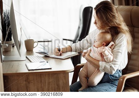 Serious Young Mother Sit At The Table, Hold In Arms Little Daughter, Beautiful Lady Making Notes, Pl
