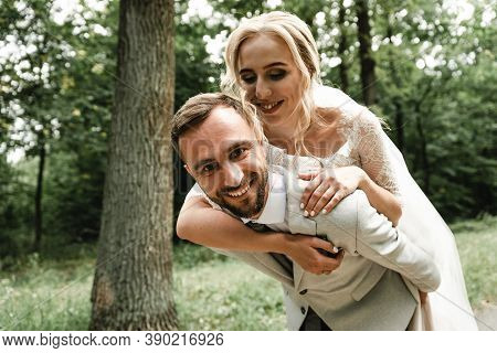The Bride Gently Hugs The Groom From The Back And Happily Whispers In His Ear The Kind Words On The