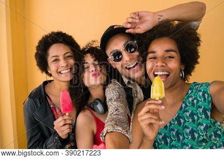 Multi-ethnic Group Of Friends Enjoying Summertime While Eating Ice Cream.
