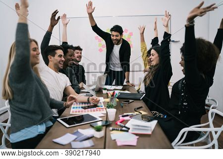 Happy Business Team Celebrating With Raised Up Hands In The Office. Success And Winning Concept.