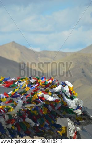 Buddhist Prayer Flags Of All Colours Fluttering In The Breeze On A Mountain Peak. Behind Is A Mounta
