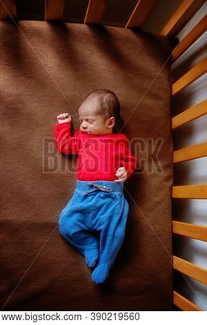 Cute Newborn Baby. Sleeping Baby On A Dark Background. Closeup Portrait Of Newborn Baby. Baby Goods