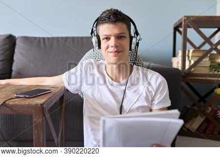 Teenager Student In Headphones With Notebook And Smartphone Studying. Guy Sitting At Home On Floor,