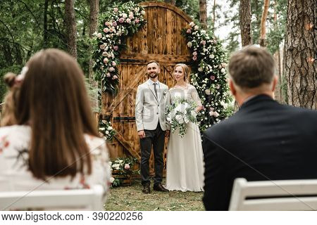 Wedding Day Of The Bride And Groom,the Groom And The Bride Stand Near The Wedding Decorations Where