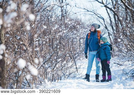 Woman With A Child On A Winter Hike In The Mountains. The Boy Travels With Mother In The Cold Season