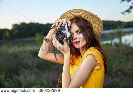 Woman Holding Camera Looks Into The Camera Lens Red Lips Hat Nature Fresh Air Lifestyle