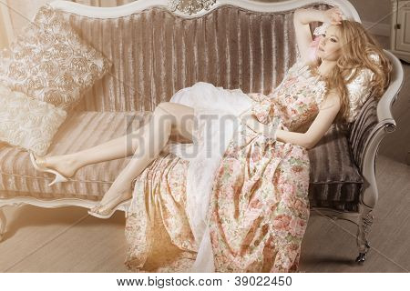 Stylish young woman in a vintage dress in a luxurious interior