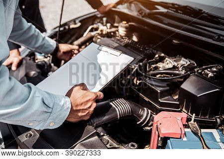 Auto Mechanic Using Checklist For Car Engine Systems After Fixed. Concepts Of Car Insurance Support