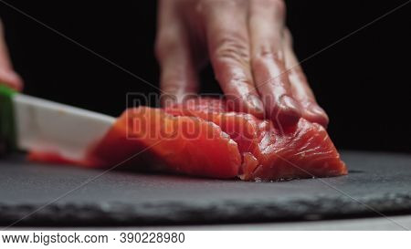 Sushi Chef Slices Fresh Salmon On The Sushi Bar. Chef Cutting Salmon Fillet At Professional Kitchen.