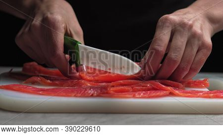 Male Chef Cuts Fillet Of Fresh Salmon Into Large Chunks. Cooking Fish In Kitchen. Preparation Of Ing