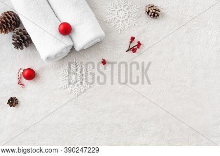 Christmas Spa Concept And Winter Skin Care Products, Pine Cones And Snowflakes On White Soft Towel B