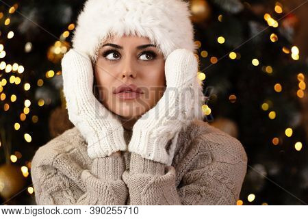 Young Woman In Winter Clothes Looking Upover Lights Background-season, Christmas, Holidays And Peopl