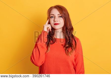 Young Adult Girl Posing With Pensive Look, Holding Finger On Temple. Attractive Woman In Orange Swea