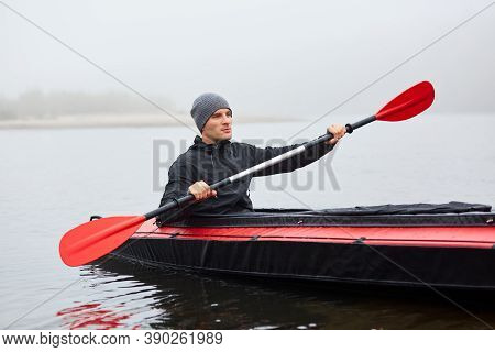 Man Paddles Red And Black Kayak With Paddle In Middle Of River Or Lake In Fall Season. Autumn And Wi