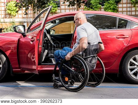 Young Handicapped Driver Getting In Red Car Fom Wheelchair