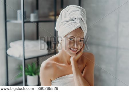 Beautiful European Woman With Makeup Touches Skin, Has Minimal Makeup, Has Healthy Glowing Skin, Wra