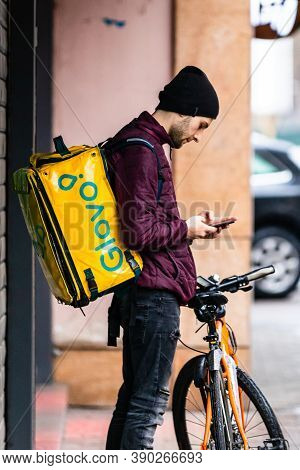 A Glovo Food Delivery Courier On A Bike. Restaurants Are Closed And Only Deliveries Are Allowed Duri