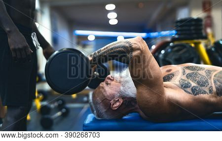 Senior Fit Man Weight Lifting With Personal Trainer In Gym Sport Club - Mature Bodybuilder Doing Wor