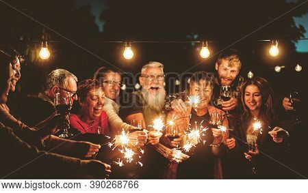 Happy Family Celebrating With Sparklers Fireworks At Night Party - Group Of People With Different Ag