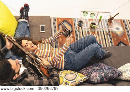 Happy Couple Recording Video With Mobile Tablet While Playing Guitar At Home - Young Romantic Lovers