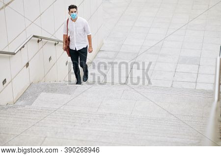 Serious Young Man In Medical Mask Walking Up The Stairs In The City