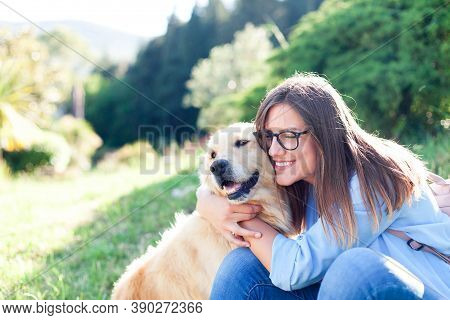 Young Woman Hugging Beautiful Dog. Happy Girl And Labrador Retriever Cuddle Together In Park. Lifest