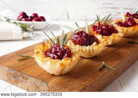 Holiday Phyllo Pastry Appetizers With Cranberries And Baked Brie. Serving Board Closeup Against A Wh