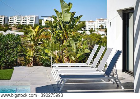 White Empty Deck Chairs In Row Near Swimming Pool. Summer Holidays And Travel Concept