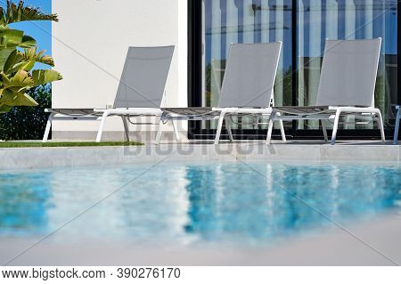 On Poolside Empty Sun Beds At Summer Sunny Day. Summertime Holidays And Tourism Concept