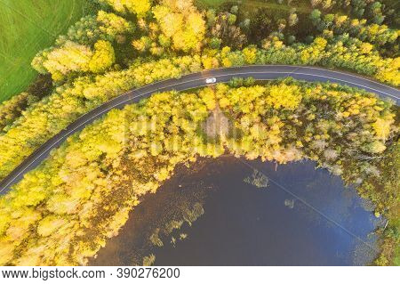 Aerial View Of Rural Road With White Car In Yellow And Orange Autumn Forest. Aerial Road Near The La