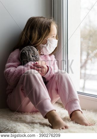 Covid-19 Coronavirus Concept, Sad Kid In Medical Mask Looks Out Window In House. Pensive Child Sits