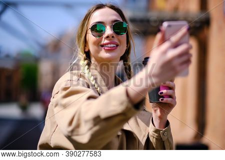 Closeup happy hipster girl doing selfie photo by mobile phone outdoors. Cheerful woman holding cellphone on city street. Laughing woman pulling faces with mobile phone in urban background.