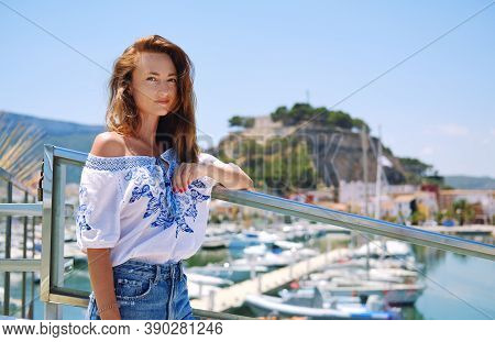Beautiful 30s Woman Pose On Denia Castle And Marina Background.  Historical Coastal City In Province