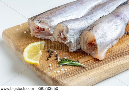 Raw Fresh Pollock Fish On A Wooden Board With Lemon, Rosemary And Spices.