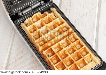 Fresh Hot Belgian Waffles Cooked In A Waffle Iron On A White Wooden Table. Close-up