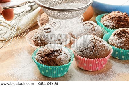 Freshly Baked Homemade Muffins Pouring In Powdered Sugar On Wooden Table. Homemade Cakes.