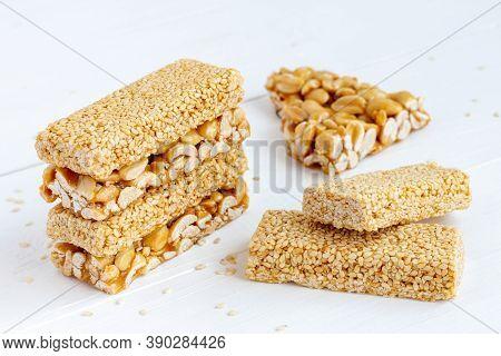 Peanut And Sesame Brittle Bars (indian Peanut Chikki) On White Wooden Background.