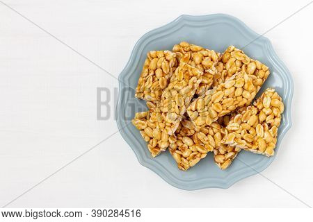 Plate Of Peanut Brittle Candy Pieces. Top View On A White Wooden Background.