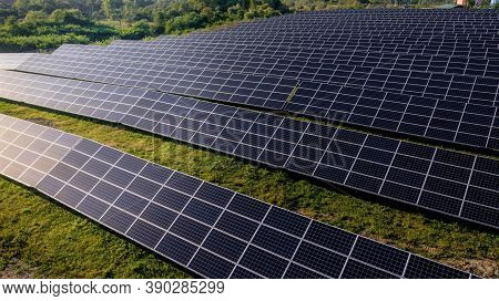 Solar Power Station In Green Field On Sunny Day. Aerial View. Solar Panels Stands In A Row In Field