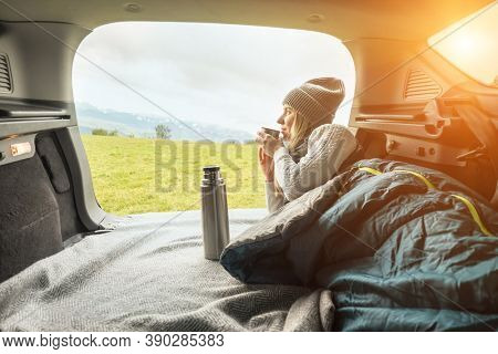 Girl resting in her car. Woman hiker, hiking backpacker traveler camper in sleeping bag, drinking hot tea and relaxing on top of mountain. Health care, authenticity, sense of balance and calmness.