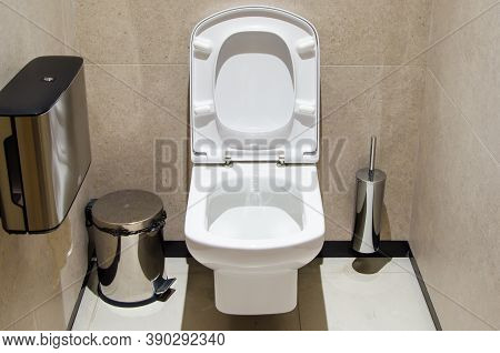 White Toilet With The Lid Raised In The Booth Of A Public Toilet. Public Restroom For Men And Women.