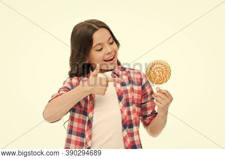 Look At This. Little Girl Point At Candy Isolated On White. Small Child Smile With Hard Candy On Sti