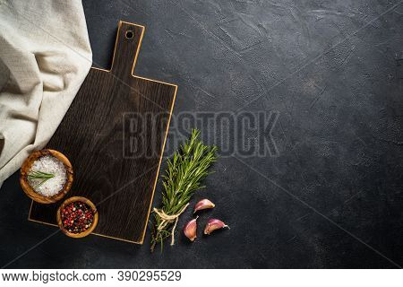 Food Cooking Background On Black. Black Wooden Cutting Board, Herbs And On Black Stone Table. Top Vi