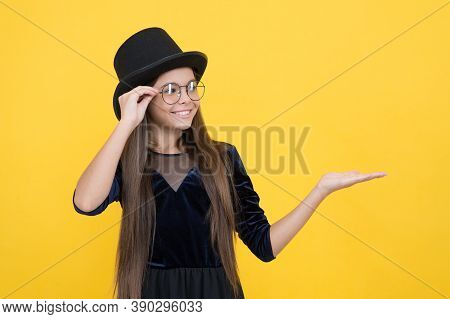 Presenting Product. Happy Girl Hold Empty Hand Yellow Background. Fashion Marketing. Sales Presentat