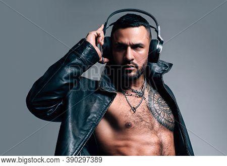 Music In Headphones. Bearded Hispanic Man With Muscular Torso Wearing Headphones. Brutal Latino Man