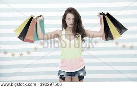 Strong Shopaholic Girl Hold Shopping Bags. Beautiful Shopaholic. Girl Holding Colorful Paper Bags In