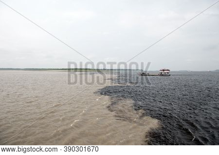 Water Meeting In Brazil -amazon River With Rio Del Negro. Transfer Boat With Cars On Deck Floating O